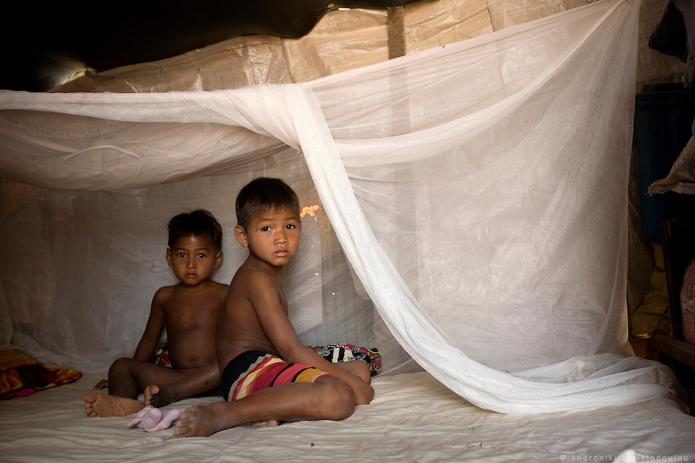 Rady 's half brothers Yort (7) (R) and Heir (4) (L) on their bed, inside their home in a remote location outside Sisophon city.