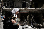 SYRIA, ALEPPO : A Syrian woman walks in front of a building on September 23, 2012, that was destroyed in an air strike by government forces, in Aleppo.ALESSIO ROMENZI