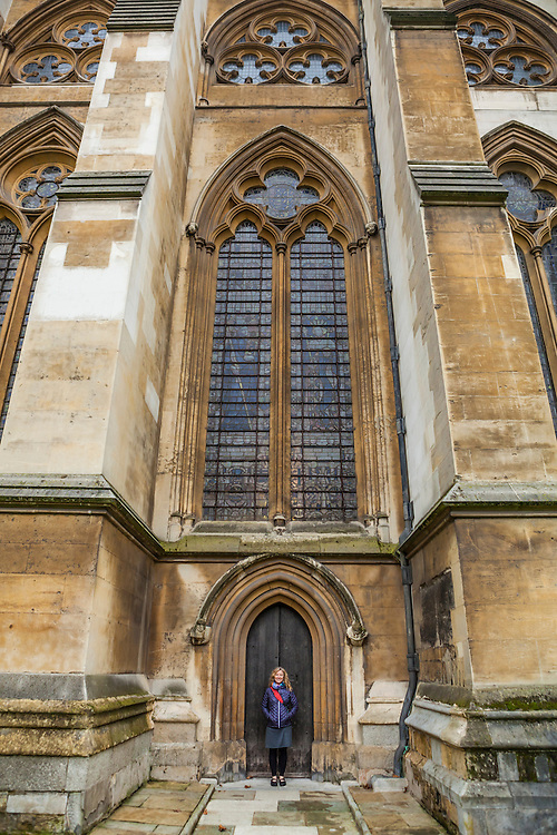A woman tourist standing in front of one of the side doors on Westminster Abbey, London, England, United Kingdom.