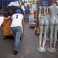 """Buhoneros - Two young buhoneros push their cart past mannequins on their way to set up their stall in the Sabana Grande neighborhood of Caracas Friday, December 15, 2006.  Buhoneros, thousands of workers who sell products from clothing and accessories to household goods and bootleg DVDs, make up the controversial """"informal economy.""""  While many Caracas residents complain that the buhoneros have taken over streets with their makeshift marketplace, many buhoneros give thanks to Venezuelan President Hugo Chavez for allowing them a way to survive by creating their own small businesses."""