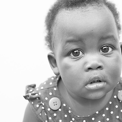 Black and white portrait photograph of lonely and scared African American baby girl