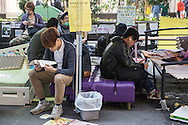 Reading and browsing on a smart phone during a quiet moment at the round-the-clock protests for democratic rights that are ongoing in Hong Kong.