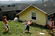 From left, Alexa Taylor, 10, Sheldon Eilers, 10, and Kimberleigh Oliveira, 10 play in the backyard of their Scotia, CA home on Tuesday, June 27, 2006. The town of Scotia in Northern California is a company town owned by the Pacific Lumber Company (PALCO), but that will change as the company will begin to sell the town. (Photo by Max Whittaker for The New York Times)<br />