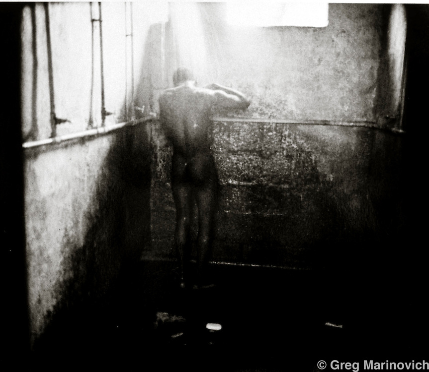 Migrant worker showers in Mamelodi hostel, Mamelodi, Pretortia, 1989. Scanned from original polaroid.