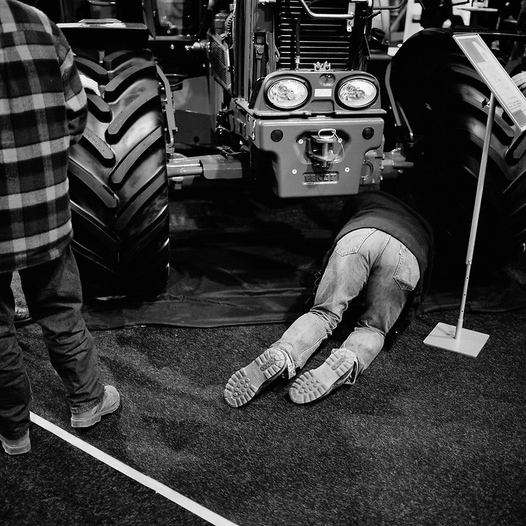 Tractor culture at Jaeren, Rogaland, Norway... A man studying some details of a tractor in a agriculture show in Stavanger, Norway..Jaeren is one of the major agricultural areas in Norway. There are tractors and traces of tractors almost everywhere. ..Photo by Knut Egil Wang /MOMENT