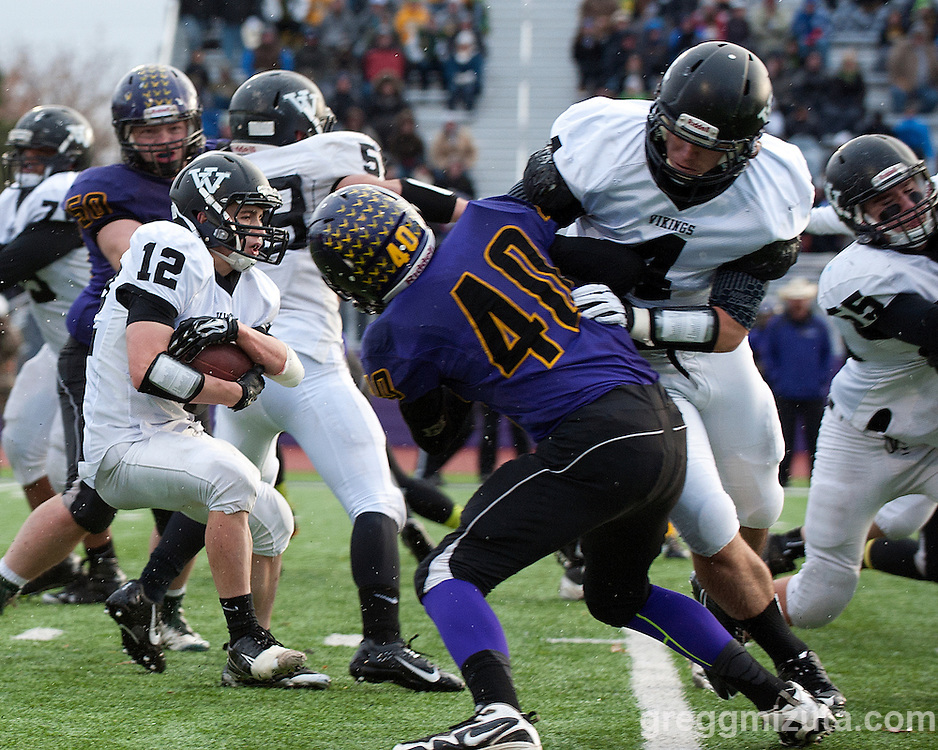 Vale junior Zac Jacobs looks for running room behind the blocks of Garret DeVos on Klayton Borden and Andrew Weber on Joey Knox during the first quarter of the Oregon 3A State Championship game at Kennison Field, Hermiston, Oregon, November 29, 2014. Vale defeated Harrisburg 45-19 to end the season with a 12-0 record and Vale's 11th state football title.<br />