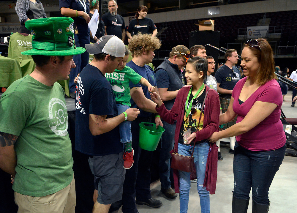 gbs031217i/RIO-WEST -- Cancer patient Leandra Tafoya, 14, with her mother, Rosina Cohen of Albuquerque, pass out pins to knights of the St. Baldrick Foundation during the New Mexico Firefighters Event for the St. Baldrick's Foundation which raises money for childhood cancer research at the Santa Ana Star Center on  Sunday, March 12, 2017. Knights have participated in being shaved or volunteering from 7 to 9 years. (Greg Sorber/Albuquerque Journal)