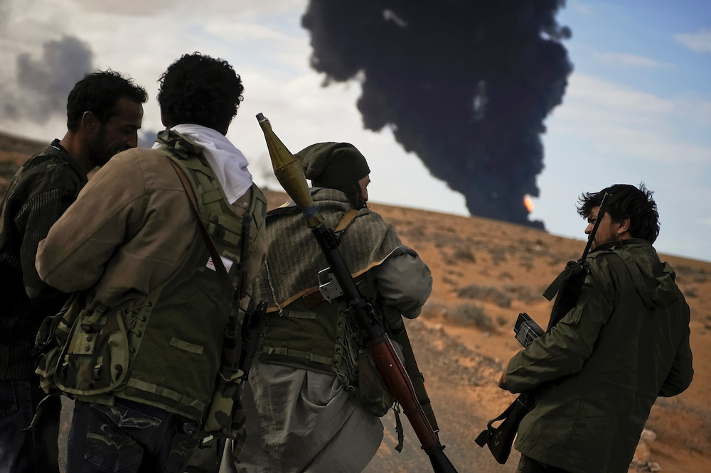 Black plumes of smoke surround rebel forces as they take heavy machine gun fire and artillery shelling during an air strike on Wednesday, March 9, 2011 while advancing between the oil port of Ras Lanuf and Bin Jiwad, Libya.  Medics working with opposition forces in eastern Libya are reporting over 400 rebels have been killed by pro-Qaddafi forces in the region since the uprise began.
