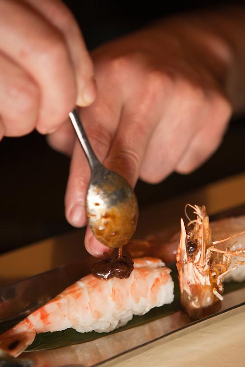 Chef Noriaki Yasutake decorates a piece of shrimp sushi with a tangy sauce.