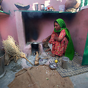 Rajasthani woman prepares chai (tea) in a typical kitchen with a chulha (oven) and making use of firewood.