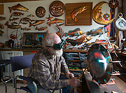 Copper artist Clark Mundy and his work in his Port Angeles WA studio. He is renowned for his sculptures of salmon, native American masks, and sea life, all made from sheet copper. He creates them using a simple array of tools: copper snips, a torch for heating and annealing the metal, copper welding rod, and small tools for hammering the metal into shapes of his design. HERE: He anneals (heats) the copper to red-hot to soften it for shaping with hammers and tools.