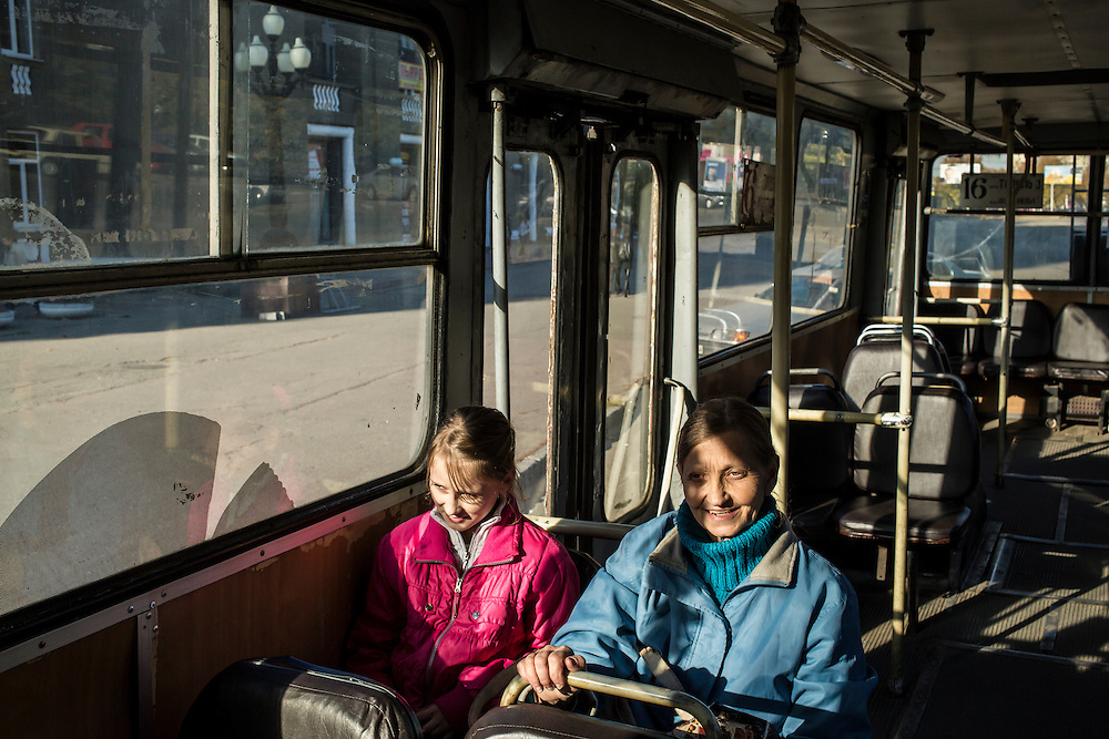 DNIPROPETROVSK, UKRAINE - OCTOBER 12: Yeva, 10, and her grandmother, Svitlana Kostromina, ride a bus on the long trip from the Good News Evangelical Church to the home where they are living with a family that is part of the congregation on October 12, 2014 in Dnipropetrovsk, Ukraine. Yeva and her family fled fighting in Luhansk. The United Nations has registered more than 360,000 people who have been forced to leave their homes due to fighting in the East, though the true number is believed to be much higher.(Photo by Brendan Hoffman/Getty Images) *** Local Caption *** Svitlana Kostromina