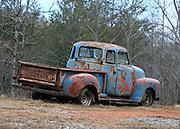 A 1950-something Chevrolet pick up truck sitting in a field near Blue Ridge Georgia.