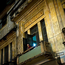 A Vietnamese woman stands on the balcony of an old French Colonial house in Ho Chi Minh City, Vietnam, Southeast Asia.