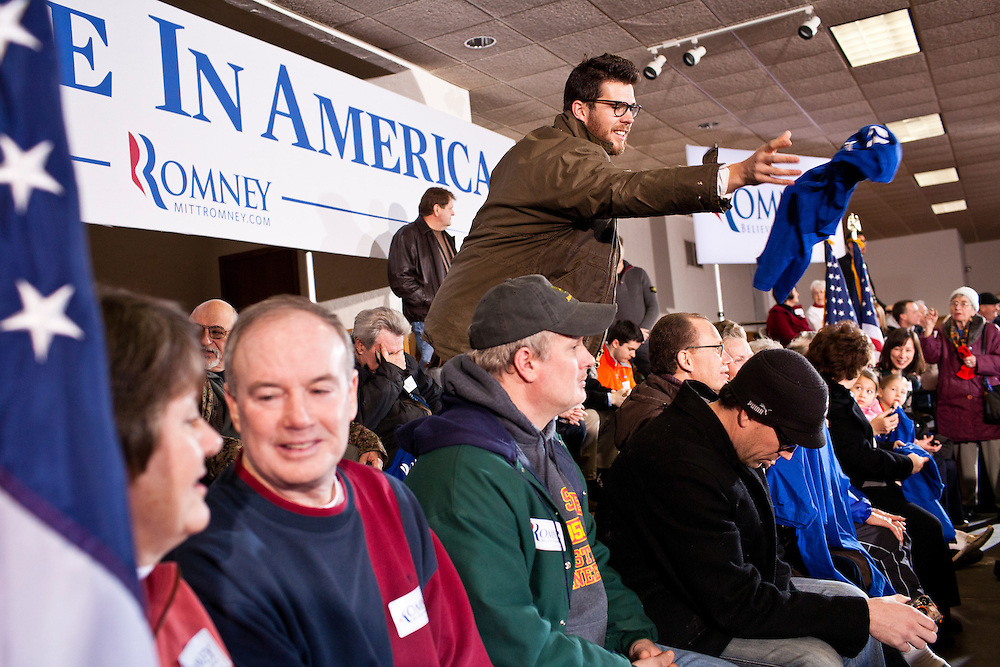 A campaign worker tosses out shirts to the audience before Republican presidential candidate Mitt Romney holds a campaign rally at the Mississippi Valley Fairgrounds on Monday, January 2, 2012 in Davenport, IA.