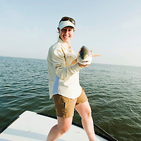 Fisherwoman shows her Redfish caught in the Laguna Madre off the Texas Gulf Coast.