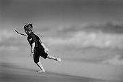A boy in a wet suit plays gleefully beside the Pacific Ocean in Huntington Beach, California.