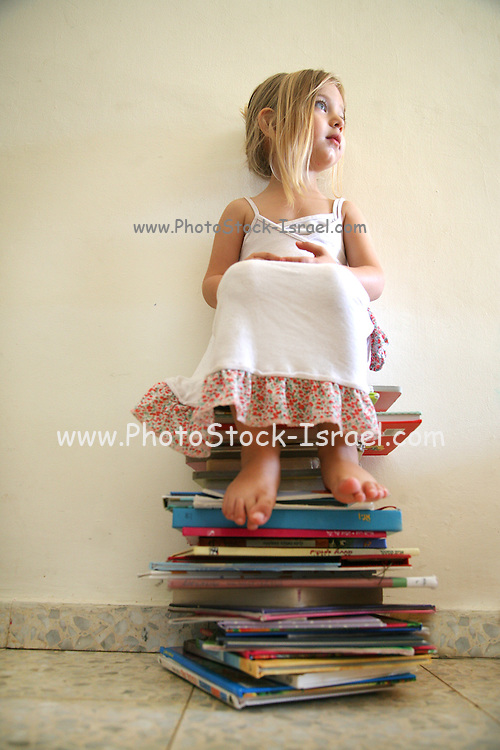 Girl of three sits on a stack of books looks to the right