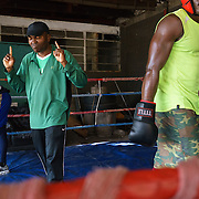 Trainer James Ike offers stern words of advice to Angel Harrison (left) and Yomi Shokunbi (right) between rounds of sparring at the Hillbrow Boxing Club. Both boxers are aspiring professionals, hoping to qualify for their boxing licences.