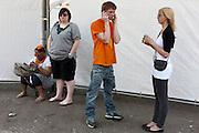 Mensen zoeken een rustig plekje op om even te bellen en te SMS-en. In Utrecht wordt volop Koninginnedag gevierd met een vrijmarkt, bandjes, bootjes en gewoon lekker liggen in de zon.<br /> <br /> People are looking for a quiet spot to make a telephone call and sending text messages at Queensday in Utrecht.