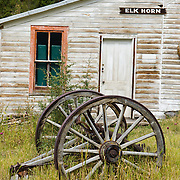 An old iron rimmed wooden wagon wheel ages in front of a private white-washed building near Elkhorn State Park, Montana, USA. The silver, gold and lead mines at Elkhorn began booming in 1875, then declined in 1892 as silver prices dropped. A few miners still work the Elkhorn mines and live in private homes in this historic State Park within Beaverhead-Deerlodge National Forest.