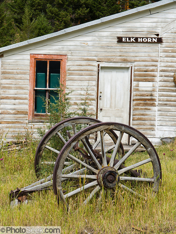 An old iron rimmed wooden wagon wheel ages in front of a for Cost of building a house in montana