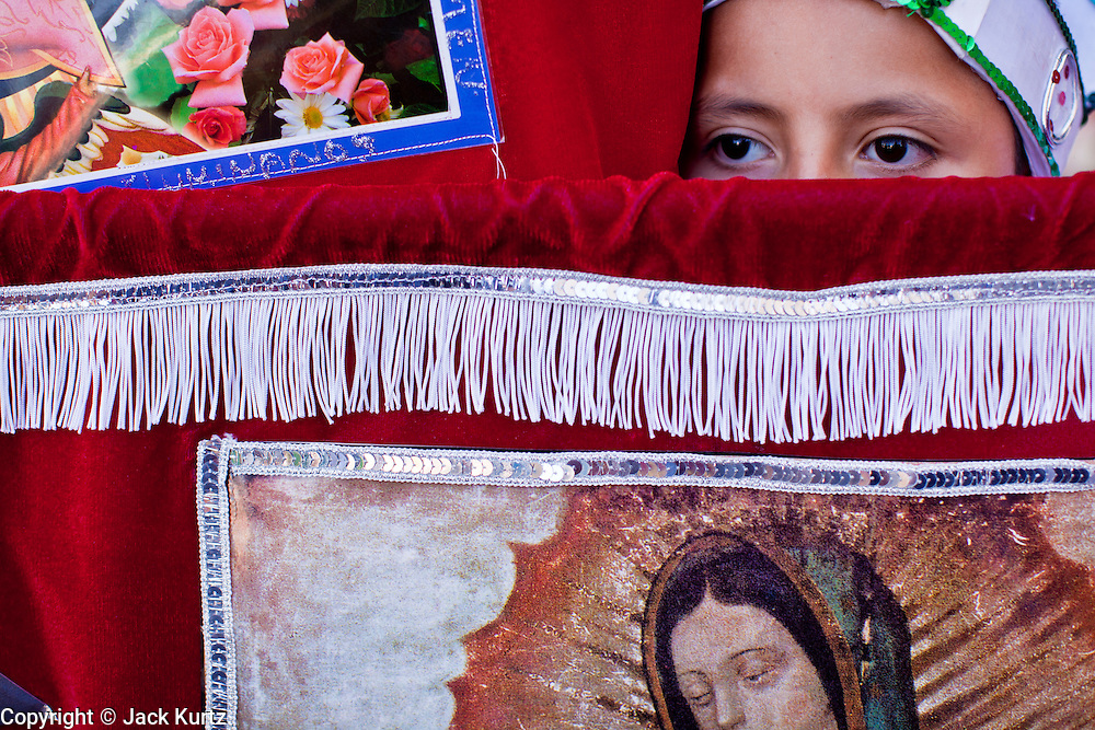 """10 OCTOBER 2010 - PHOENIX, AZ: A boy carries a tapestry with the Virgin of Guadalupe on it in Phoenix, AZ, Sunday. About 500 people processed through downtown Phoenix Sunday afternoon to honor the Virgin of Guadalupe, the """"Queen of the Americas."""" The procession was accompanied by 12 Matachine dance troupes. The Matachines are an important part of Mexican Catholic culture. They represent the battle of Good vs. Evil and the protect the Virgin from malevolent forces, represented by the demon like figures who accompany the dancers.      Photo by Jack Kurtz"""