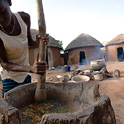 Mariam Alhassan, 11, helps her mother cook dinner inside the compound where they live in the village of Ying, northern Ghana, on Monday June 4, 2007.