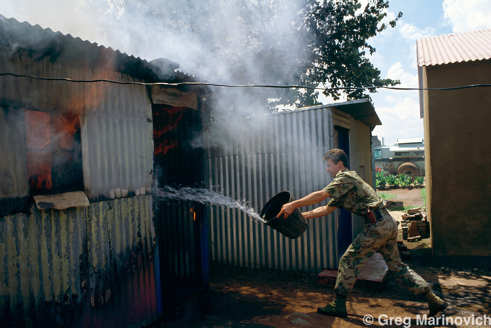 Bekkersdal Township, South Africa, Feb 1994: Riot Police try to quell a fire in a shack as they patrol during three way clashes between security forces, ANC members and  AZAPO supporters in the far West Rand township of Bekkerdal, South Africa.
