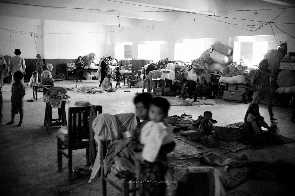 Different families sleep together in a school building in Kamari town on the outskirts of Karachi after the 2010 flood destroyed their homes and they were uprooted from their villages. All over Pakistan schools, colleges and other government buildings were being used as temporary shelter for flood affected families. For women and girls especially, lack of privacy was a big problem. The lack of hygiene became another concern, with many people developed skin infections, diarrhea and other diseases. Karachi, Pakistan, 2010