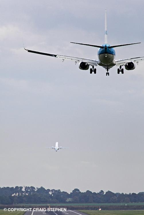 A plane landing and one taking off at Edinburgh airport, Scotland, UK