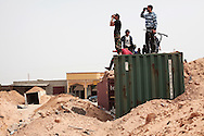 Observing a long and  empty stretch of road toward Zliten, Libyan rebels on the watch for Gadhafi's forces incursion at a road block made of shipping containers and sand berms on Al Dafniyah front line, 25 km west of Misrata.  22 May 2011.