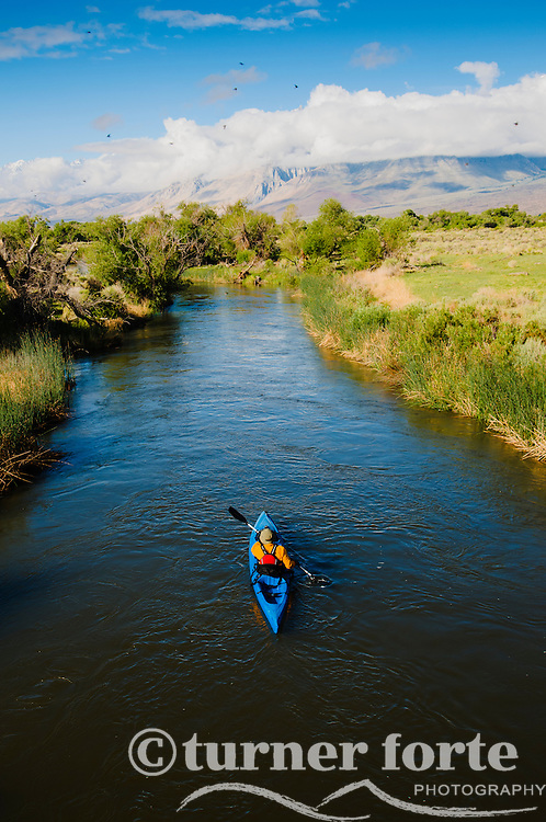 A kayaker paddles down Owens River while clouds move across the Eastern Sierras, California.