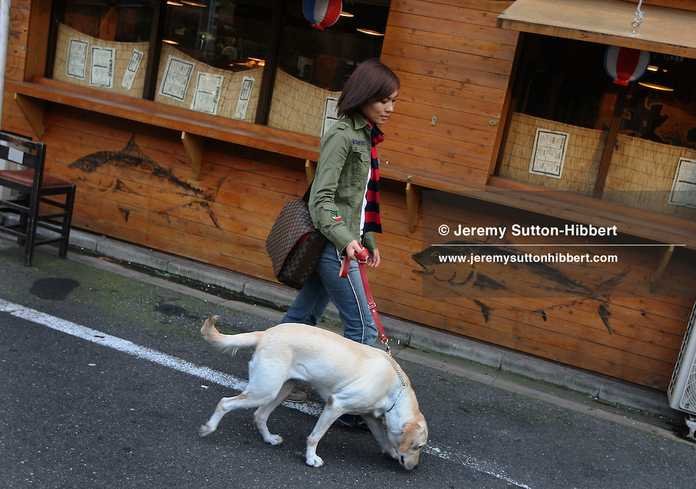 "Saori 'Aya' Soejima, aged 31, walking a dog,called  'Rolo' (aged 3.5yrs),  that she rents by the hour from 'Dog and Cafe Bar Janet Village"", in Gotanda district,  Tokyo, Japan, Thursday, Nov. 8th, 2007. Saori Soejima has rented Rolo the labrador more than 40 times, and as a Gold Card Member of the rental shop she pays Japanese Yen ¥1,600 per hour, as opposed the usual price (for non-gold members) of ¥2,100 per hour."