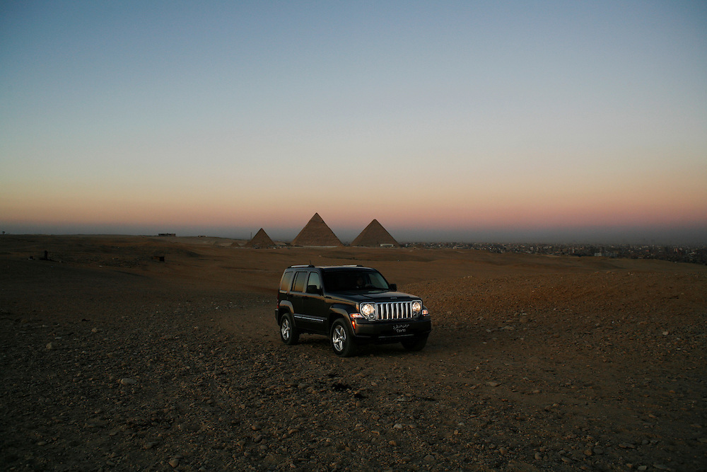 A jeep drives in the desert next to the pyramids in Giza, just outside Cairo.