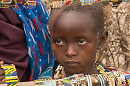 This little girl helps her mother sell jewelry to visitors.
