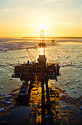 Alaska. Oil and gas production platforms in icy Cook Inlet stand silouetted by the golden setting sun.