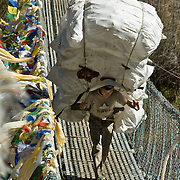 """A porter carries a huge load of empty recyclable bottles over Larja Bridge (strung with Tibetan Buddhist prayer flags), over Dudh Koshi (Kosi=river) below the town of Namche Bazaar, Nepal. Sagarmatha National Park was created in 1976 and honored as a UNESCO World Heritage Site in 1979. Published in """"Light Travel: Photography on the Go"""" book by Tom Dempsey 2009, 2010."""