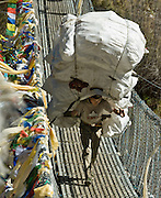 "A porter carries a huge load of empty recyclable bottles over Larja Bridge (strung with Tibetan Buddhist prayer flags), over Dudh Koshi (Kosi=river) below the town of Namche Bazaar, Nepal. Sagarmatha National Park was created in 1976 and honored as a UNESCO World Heritage Site in 1979. Published in ""Light Travel: Photography on the Go"" book by Tom Dempsey 2009, 2010."