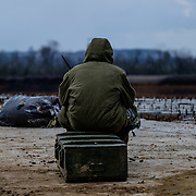 We heard sever shelling at the drone camp. Soldier in post with his radio, staring at the ennemy direction and listen to the order to be prepare to evacuate or go into the fight.