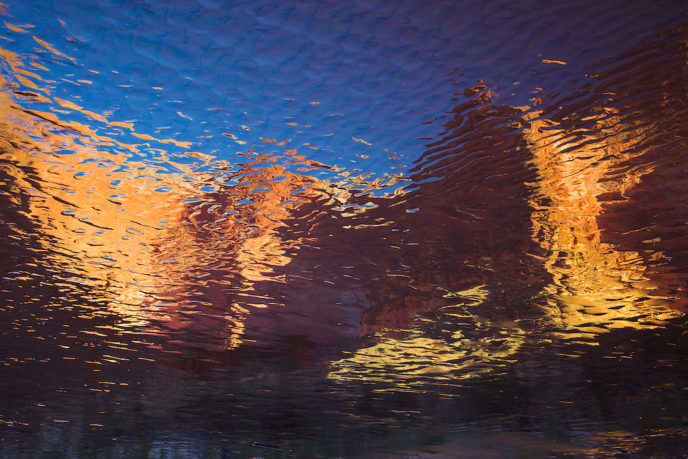 The sandstone walls of the Grand Canyon reflect in the Colorado River.