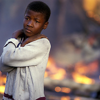 Haiti, Port-au-Prince, Boy stands outside house burned during election violence in Haitian capital
