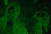 Bill Gibson and Mike Brumfield look through night vision equipment while searching for Bigfoot in rural Alabama on October 19, 2013.