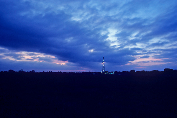 Stock photo of an oil and gas drilling rig at sunset in Texas