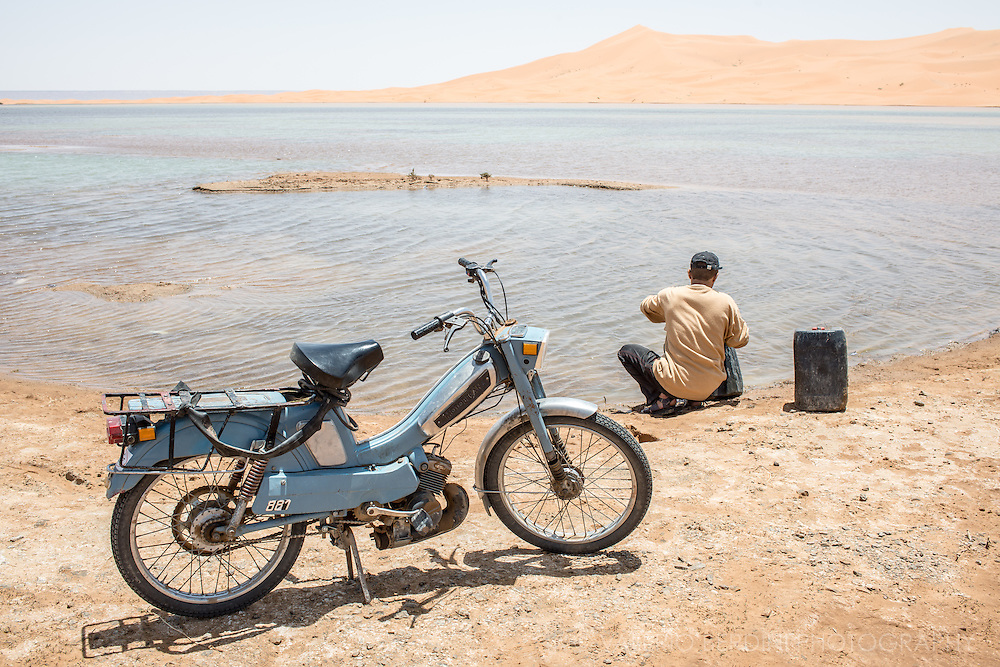 A man working in a building site close by drove his moped to a lake next to Sahara dunes to fetch some water tanks. Despite common belief sandy desert is often reach in water.