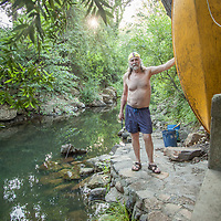 George Meyer stands next to the Napa River at the base of his house at the corner of Third and Washington in Calistoga, CA