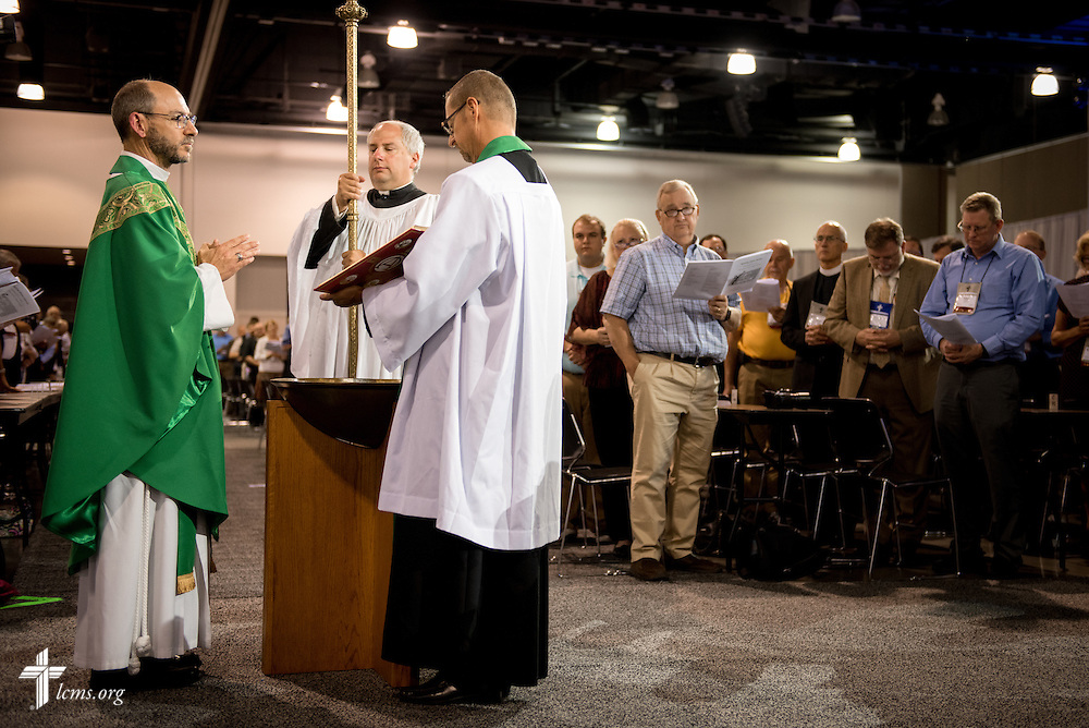 The Rev. Peter C. Bender, pastor of Peace Lutheran Church in Sussex, Wis., reads the Gospel during the Opening Divine Service of the 66th Regular Convention of The Lutheran Church–Missouri Synod on Saturday, July 9, 2016, at the Wisconsin Center in Milwaukee. Bender is joined by the Rev. Will Weedon, chaplain of the LCMS International Center (right) and the Rev. Allen Braun, pastor of Mount Hulda Lutheran Church in Cole Camp, Mo. LCMS/Erik M. Lunsford
