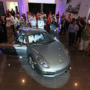 Attendees of 2014 Cayman S Unveiling inspect the new Porsche during the Porsche Cayman S Unveiling event Thursday, May. 2, 2013, at Porsche of Delaware in Newark Delaware.