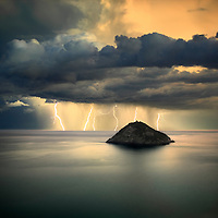 "A mighty thunderstorm off the Ligurian coast near Bergeggi, Italy. This is a multiple exposure consisting of 5 shots of 15"", each with at least a bolt in it. Taken from a vertical cliff about 100 meters above the sea level, on a evening of November, a few minutes after sunset. Notes about the technique: I initially took a single exposure of 90"" of the same scene, with more or less  the same number of lightning bolts in it. Unfortunately with 75"" of exposure the clouds were badly blurred, and that's the reason why I opted for taking a number of faster exposures to be combined together. I noticed that the lightnings had quite a regular pace - more or less one every 10"" - so I simply realized that by keeping the shutter open for 15"", I would have easily recorded at least one bolt on each exposure. I did this for about 12 times, and then I chose the best 5 images to be stacked together. With this ""trick"", I've been able to produce an image with more or less the same number of bolts as the one exposed by 75"", but with the clouds far less blurred. ."