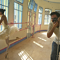 Model relased photo of Gina, a Colombian professional ballet dancer   at ¨Los Cisnes¨Dance School in Cartagena. Spanish photographer Kike Calvo is reflected on the mirror while working.